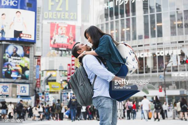 Asian couple on a trip embracing at Shibuya crossing