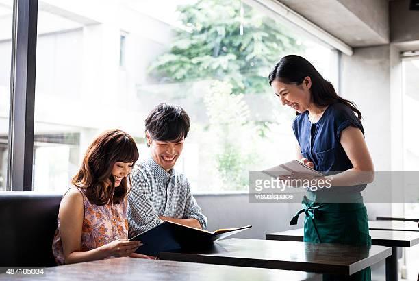 asian couple ordering food in cafeteria - klanten georiënteerd stockfoto's en -beelden