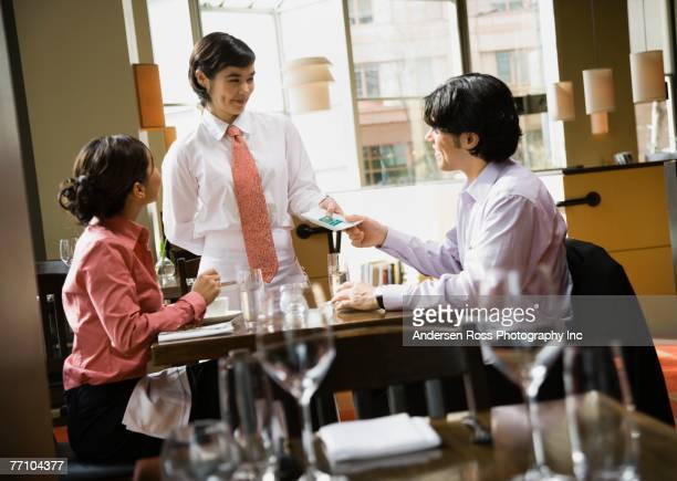 Asian couple paying bill at restaurant