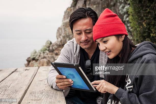 Asian couple plan scuba dive with computer tablet