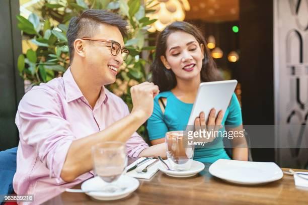 Asian couple planning on digital tablet in Kuala Lumpur Street Cafe