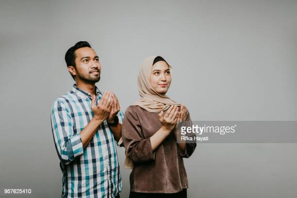 asian couple seek for forgiveness - eid al adha stock pictures, royalty-free photos & images