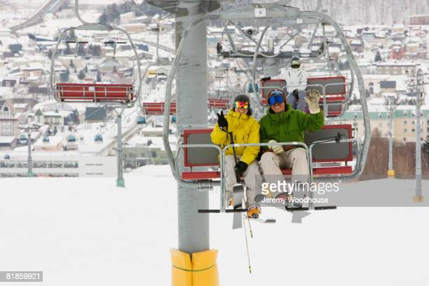 Asian couple sitting on ski lift