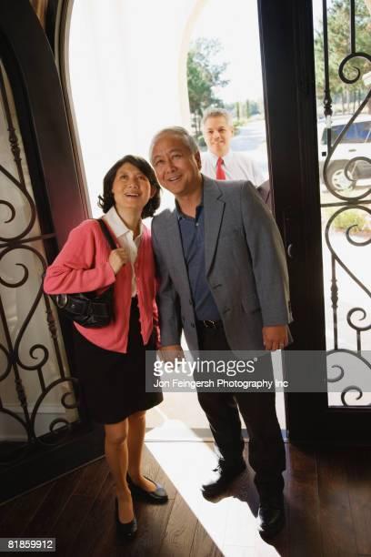 asian couple standing in doorway - ポーチ ストックフォトと画像