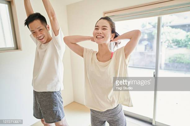 asian couple stretching exercises at home. - three quarter length stock pictures, royalty-free photos & images