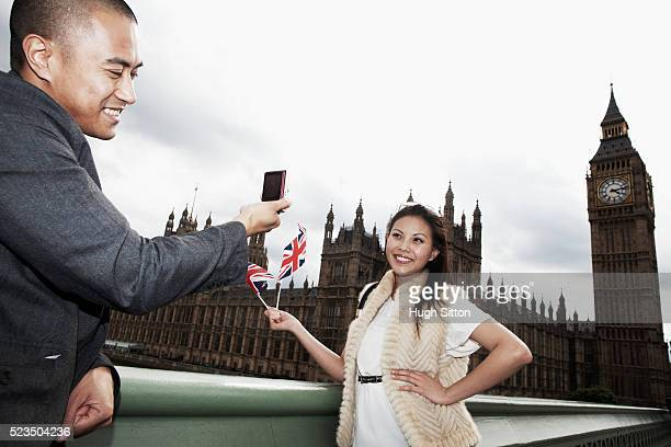 asian couple taking pictures of each other holding union jack with houses of parliament in background, london, england, uk - hugh sitton stock pictures, royalty-free photos & images