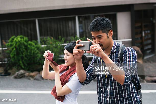 Asian Couple Taking Snapshots with Smart Phones