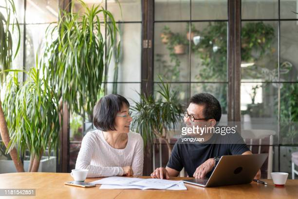 asian couple talking about buying a new house - face to face stock pictures, royalty-free photos & images