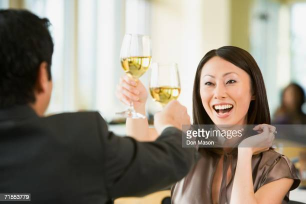 Asian couple toasting at restaurant