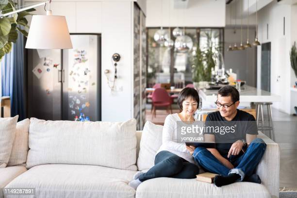 asian couple using a digital tablet on sofa - chinese ethnicity stock pictures, royalty-free photos & images