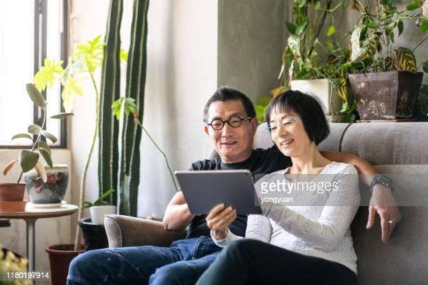 ソファでデジタルタブレットを使用してアジアのカップル - chinese ethnicity ストックフォトと画像