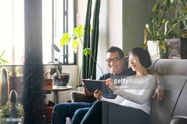 asian couple using a digital tablet on sofa - asian and indian ethnicities stock pictures, royalty-free photos & images