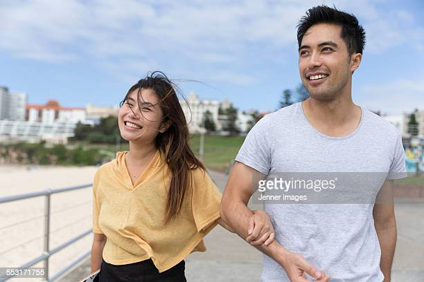 Asian couple walking together at the beach.