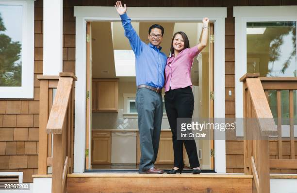 Asian couple waving in front of new house
