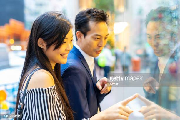 asian couple window shopping in hong kong - fashion hong kong stock photos and pictures