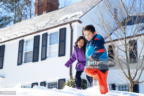 asian cousins playing outside in the snow - scarsdale stock photos and pictures