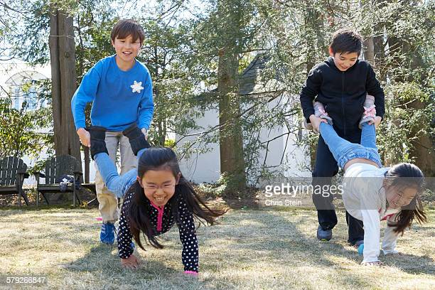 asian cousins playing wheelbarrel - scarsdale stock photos and pictures