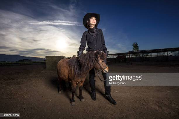 Asian Cowgirl Holding Reins of Miniature Horse