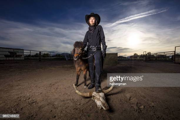 Asian Cowgirl Posing with Miniature Horse and Cow Skull