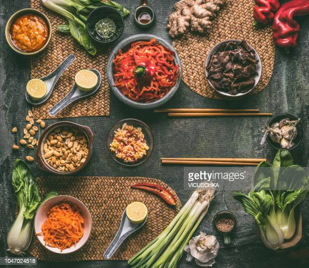 Asian cuisine ingredients in bowls with chopsticks, top view