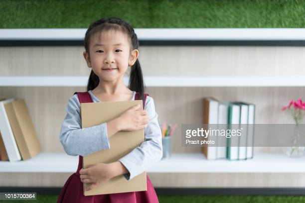 asian cute girl smiling elementary school student hugging book and looking at camera in school. - タイ人 ストックフォトと画像