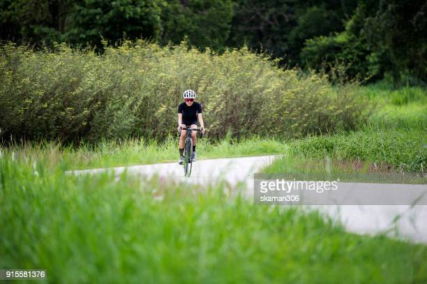 asian cyclist girl exercise and holding handle cycling on country side road by road bike (bicycle ) sport and wellness concept - wielrennen stockfoto's en -beelden