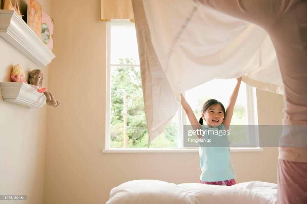 アジア娘と自宅のベッドを作り母 : ストックフォト