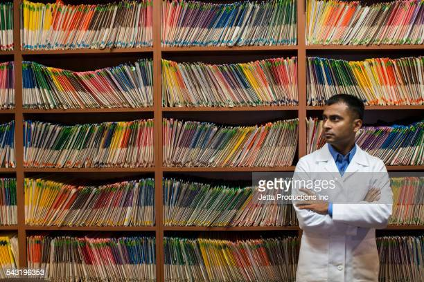 Asian dentist standing near wall of medical files