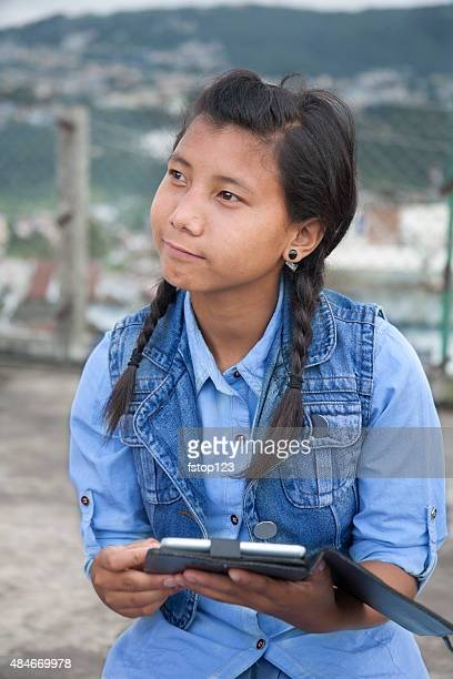 Asian descent, teenage girl using digital tablet outdoors. City.