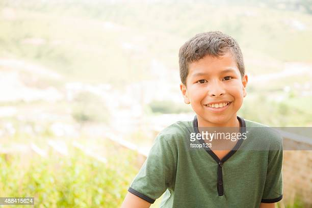 Asian descent, young boy posing on village hillside. India.