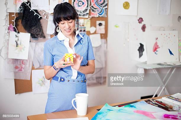 Asian designer using cell phone in studio