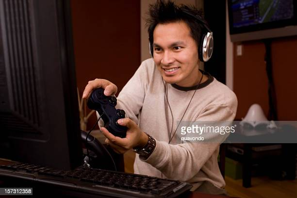 Asian Desktop PC Gamer Using Computer, Headphones, and Remote Control