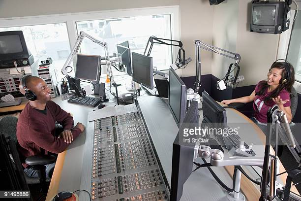 Asian dj working at radio station with co-worker