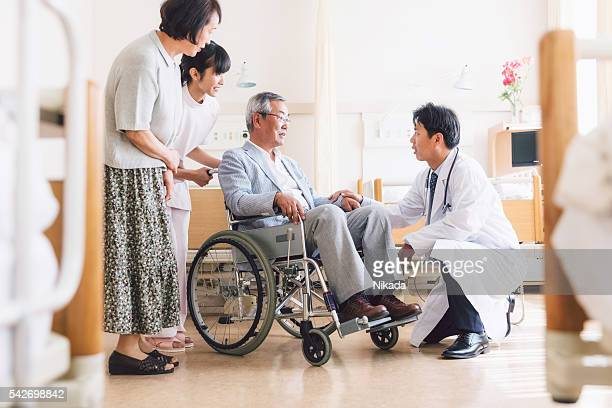 asian doctor attending to a patient in wheelchair - outpatient care stock pictures, royalty-free photos & images
