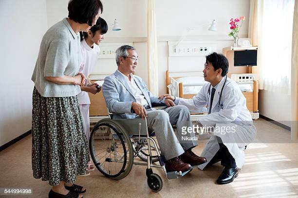 アジアの担当医師が患者の方々に車椅子