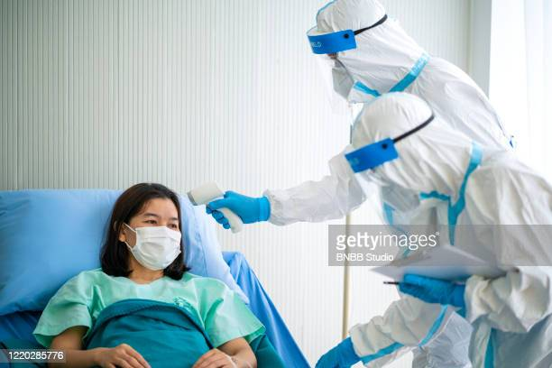 asian doctor in ppe medical suit using infrared forehead thermometer for checking coronavirus patient body temperature at hospital - temperature checkpoint stock pictures, royalty-free photos & images