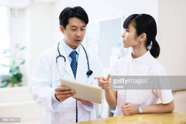 asian doctor showing digital tablet to nurse in hospital
