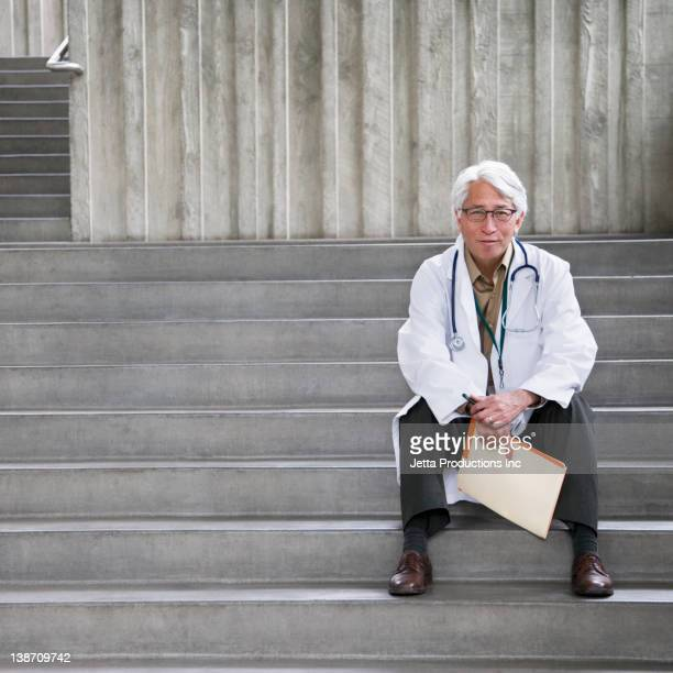 Asian doctor sitting outdoors on steps