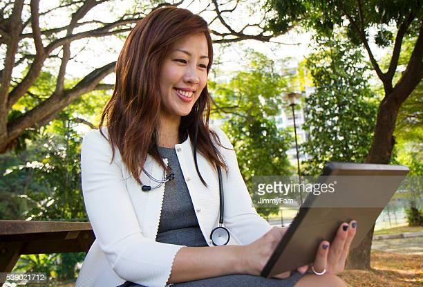 Asiatischen Arzt mit Digitaltablett im Freien