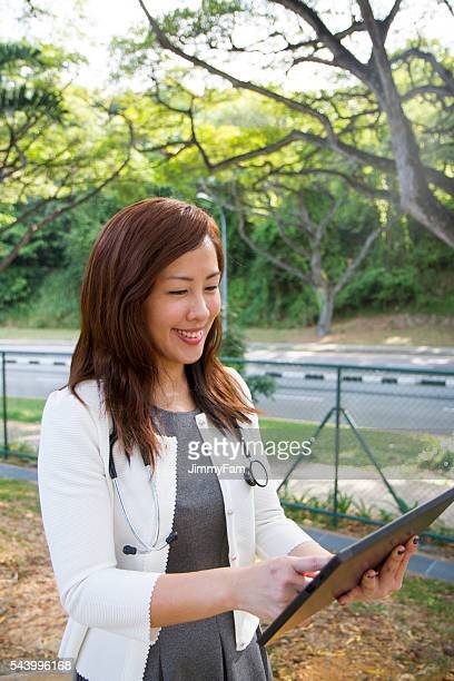Asian Doctor Using Digital Tablet outdoors