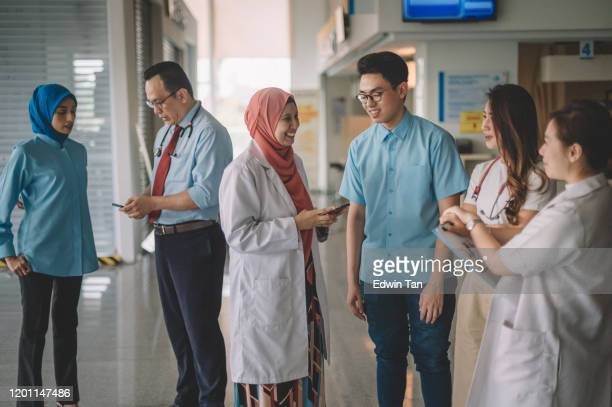 asian doctors , pharmacist and nurses having discussion in the pharmacy lobby while waiting at the entrance hall - nhs stock pictures, royalty-free photos & images