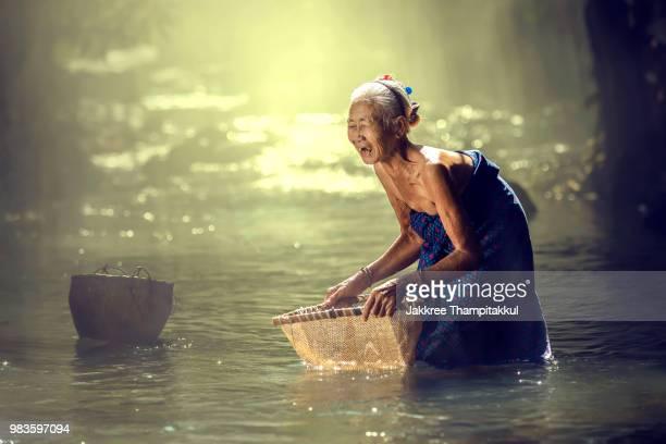Asian elderly woman happy finding fish in a streams.