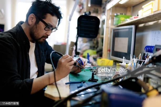 彼のスタジオのアジアの電気技師はんだ付け - 日曜大工 ストックフォトと画像