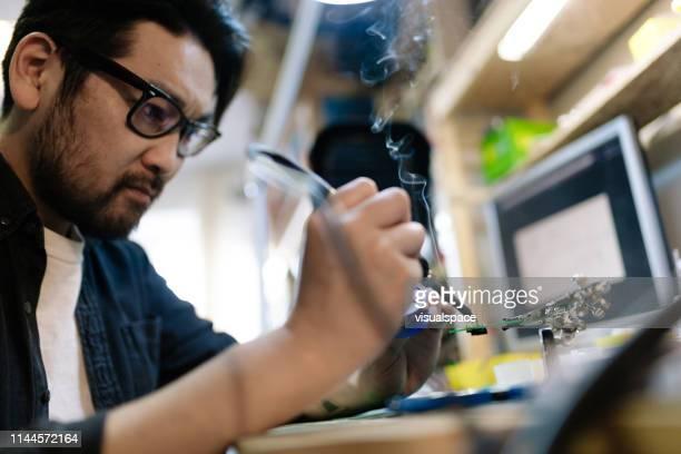 アジアの電気技師はんだ付け回路 - エンジニア ストックフォトと画像