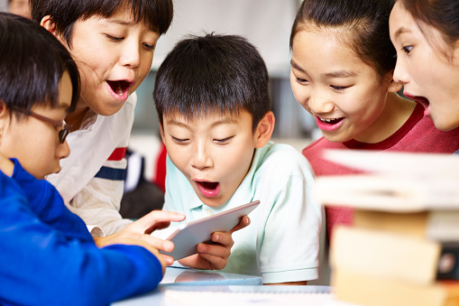 asian elementary school children playing with digital tablet during break 859303894