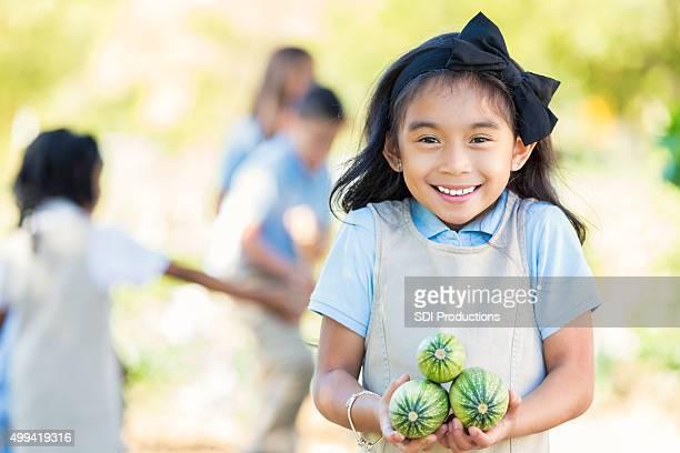 Asiatische Grundschüler holding zucchini vom Garten field trip