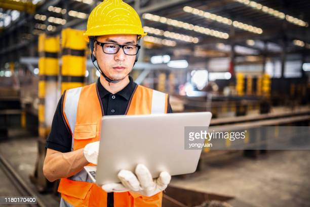 asian engineer using a laptop in a factory - chinese ethnicity stock pictures, royalty-free photos & images