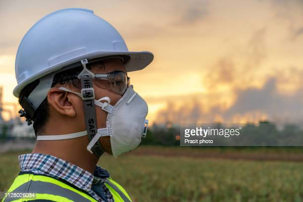 asian engineer with mask rand safety helmet in front of oil refinery and petrochemical plant with pollution - gas mask stock pictures, royalty-free photos & images