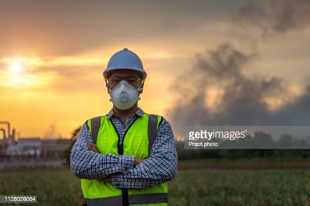 asian engineer with mask rand safety helmet in front of oil refinery and petrochemical plant with pollution - air respirator mask stock pictures, royalty-free photos & images