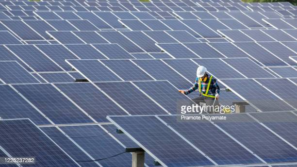 asian engineer working on checking equipment in solar power plant, pure energy, renewable energy - pannelli solari foto e immagini stock